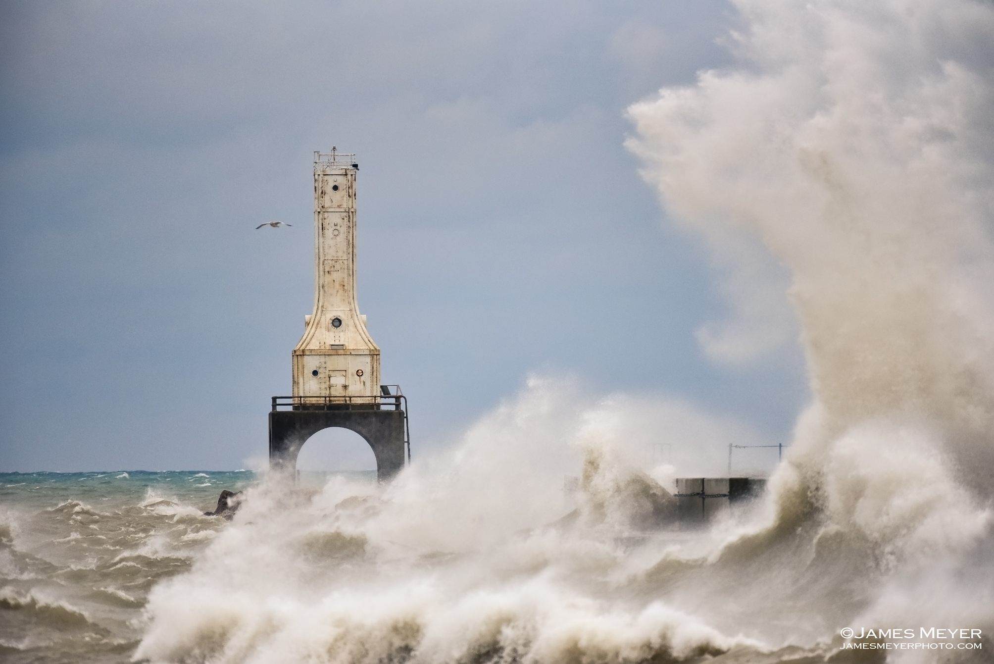Huge waves crash the shoreline and lighthouse in Port Washington WI.